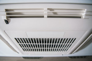 Small RV Air Conditioner. Modern Heating and Cooling Device Inside RV.