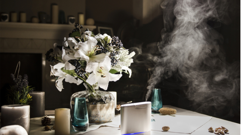 humidifier on the table near to bouquet of flowers, in home interior