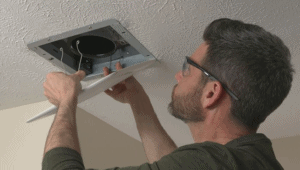 A technician working on the best bathroom exhaust fan with LED light