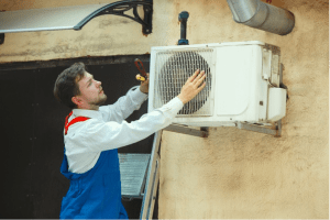 A technician inspecting an outdoor air conditioner