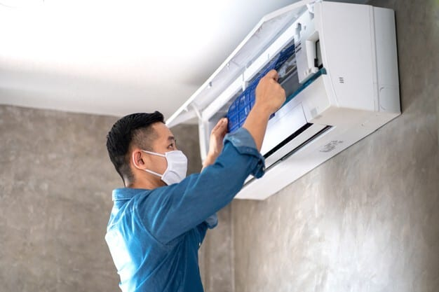 Technician inspecting a wall mounted window air conditioner